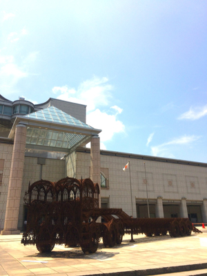 横浜美術館前に設置された、ヴィム・デルボア『低床トレーラー』(2007年)。 ゴシック様式の繊細な装飾で象(かたど)られた、全長15メートルを超える大型トレーラー。会期を通して風雨を受け、錆び付いていく様子も作品の一部として展示される。