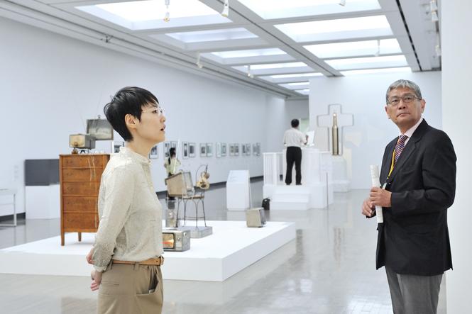 横浜美術館会場にて、天野太郎キュレトリアルヘッドの説明を聞きながら、作品に見入る菊地さん。 ©Yuichiro TANAKA
