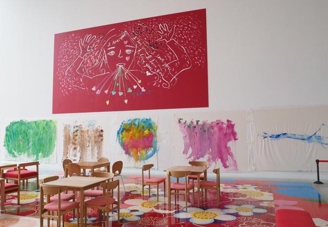 カフェスペースに展示されているラブをテーマに描いた巨大な作品《赤い女の子》2015年 ©Ellie Omiya