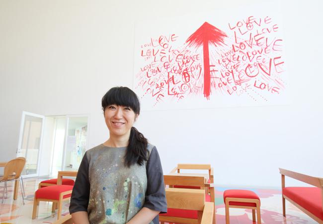 十和田市現代美術館内カフェスペースの展示作品前にて。《A DIRECTION》2013年 ©Ellie Omiya
