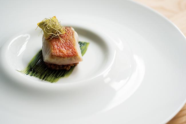 「サルモレッティ(ひめじ)と海藻」お皿のグリーンの模様はハーブのソース。蒸し煮にした魚を爽やかな味わいで。