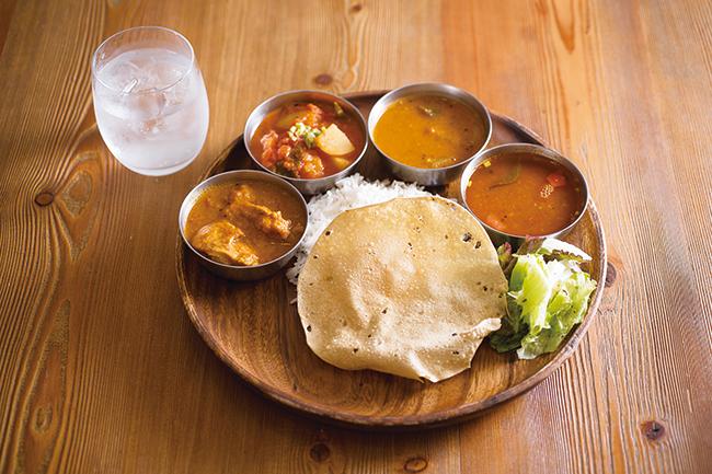 「大岩食堂のミールス」¥1,260〜 基本のミールス(¥1,260)にチキンカレー(+¥100)と本日のベジカレー/¥1,360、豆と野菜のスープ「サンバル」、薬膳スープ「ラッサム」、豆の粉で作った薄いクラッカー「パパド」、サラダ、バスマティライスが一皿に。(左上)プレミアムジントニック ¥800
