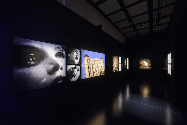 シャネル・ネクサス・ホールでの展示風景より。左側にシャネル「エゴイスト」のTVCM(1990年)からのスチール写真が見える。 © CHANEL