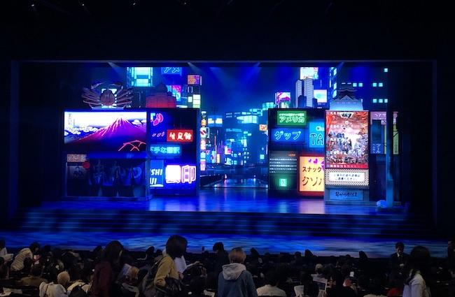 「KEREN」開演前の劇場内。ステージ上にはネオンきらめく雨の大阪の繁華街。これから何が起こるのか期待が高まる。