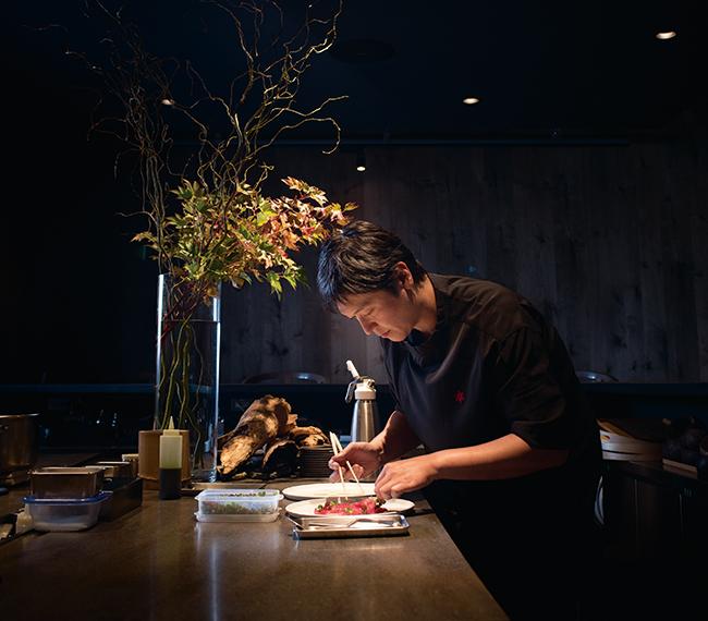 コの字形に囲まれたオープンキッチンカウンターの中、料理の仕上げに集中する「フロリレージュ」オーナーシェフ 川手寛康