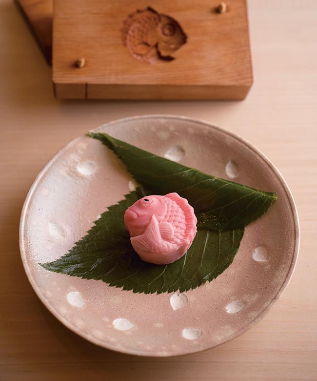 コースは昼¥8,000〜、夜¥12,000〜。鯛をかたどった春色の愛らしい茶菓子で締めくくる。中には滑らかな舌触りのこしあんと、一枚の桜の花。粋な計らいに心躍らずにいられない。丁寧に点てられた香り豊かな抹茶とともに堪能。