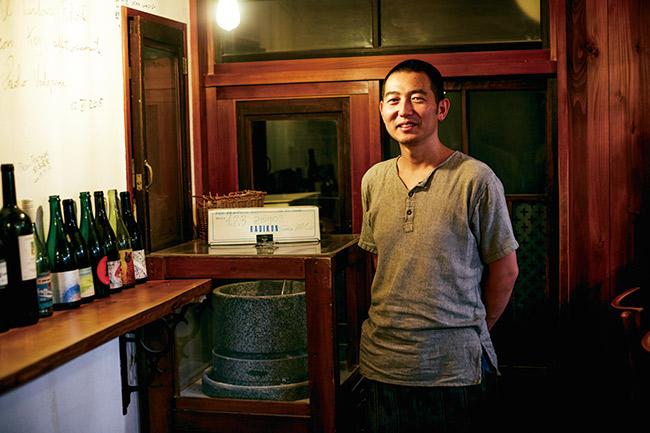 民家を改装した店内奥、石臼の前に立つオーナーの原田浩次。