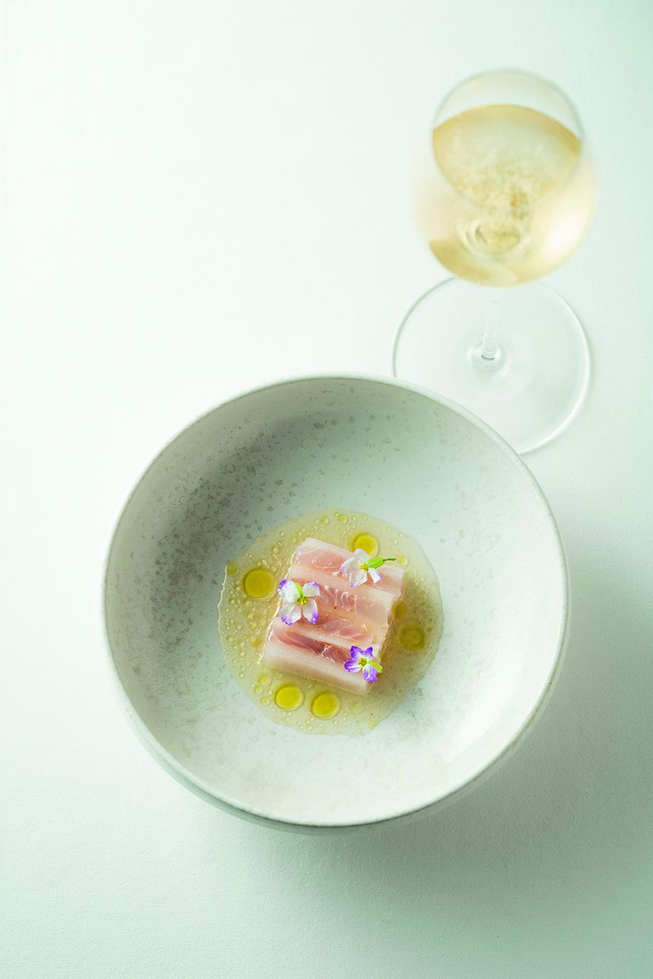 塩漬けレモンの皮や大根の花を添えた「イサキと大根のミルフィーユ仕立て」に、「クレモンペルスヴァル ブラン・ド・ブラン ブリュット」(ボトル¥12,000)を合わせて。