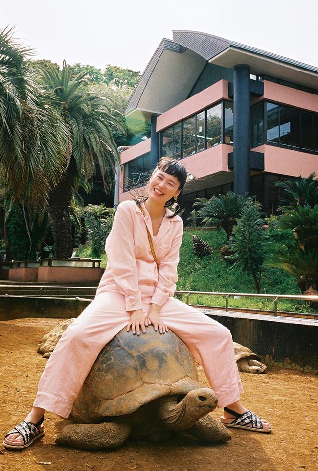 繁殖が成功して園内で飼育しているゾウガメは約70頭にもなる。園の許可もあり130歳の長老に乗って浦島太郎風。 ジャンプスーツ¥35,000/Priv. Spoons Club(プライベート・スプーンズ・クラブ 代官山本店) イヤリング¥38,000/Akikoaoki(アキコアオキ) リング¥20,000 リング¥27,000/ともにAgete(アガット) シューズ¥38,000/Charles & Keith(チャールズ & キース ジャパン)その他/本人私物