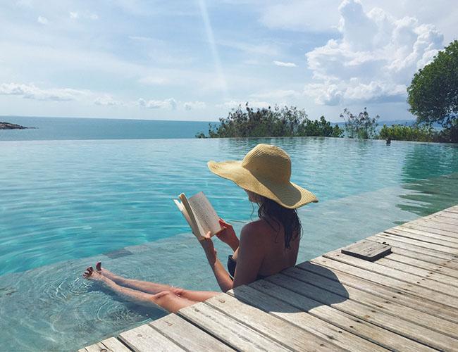 波の音を聴きながら本を読むことが一番の楽しみ。海を眺めながらプールサイドで過ごす、贅沢なひととき。