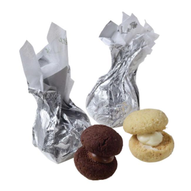 """バーティディダーマ(イタリア)各¥190。""""貴婦人のキス""""という意味の郷土菓子。(左)「ココア×ミルク」はカカオのコクのある香りと、さっくりとした生地の相性が良い。(右)「ピスタチオ×レモン×ホワイトチョコ」は、香り高いピスタチオの生地にレモンの皮を加えたホワイトチョコレートをサンド。甘酸っぱさが魅力。"""