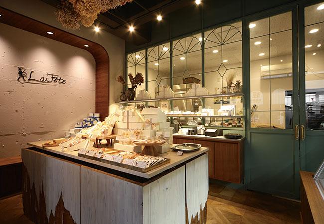 閑静な住宅街に佇む心和む愛らしいお店。ガラス越しに厨房が見える店内には、お祝い菓子が並ぶ。