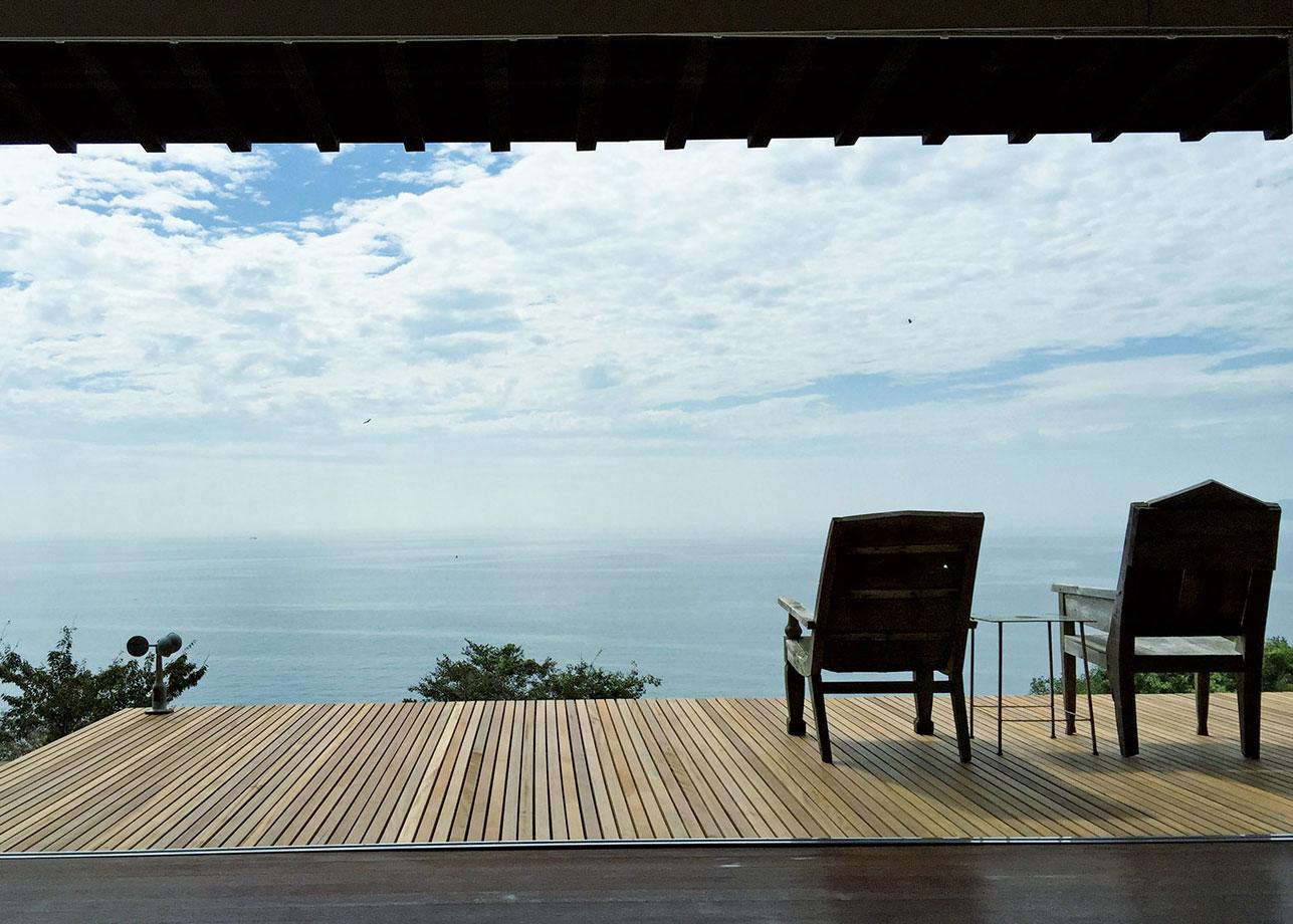 中空に突き出たようなデッキテラスは、どこまでも広がる空と海を満喫する特等席。特注の窓ガラスはすべて開放することができ、部屋にいながらにして、シームレスに自然を感じられる。