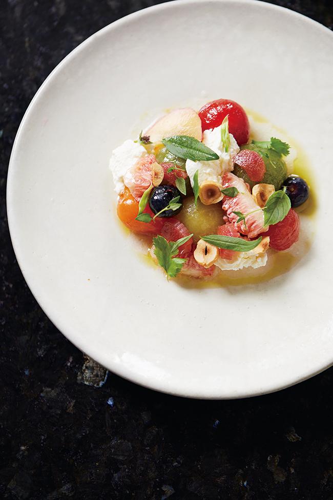 「トマトとフルーツ」。カラフルなトマト、いちじく、プラム、ブルーベリーやハーブ、リコッタチーズの爽やかな一皿。ランチ(¥2,500/¥3,000)とディナー(¥7,000)のコースの前菜。