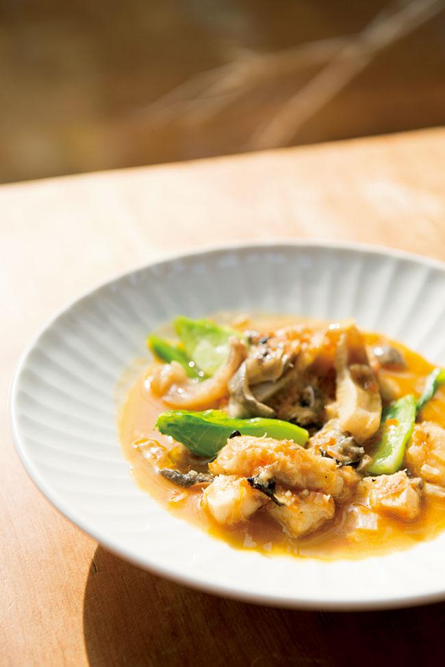 横須賀長井産の神経〆のアンコウと三浦のSHOファームの祝蕾という野菜を、スモークパプリカで煮込んだ「アンコウのトリッパ トマト煮」¥1,200。ヒレ肉や胃袋など、部位によって異なる食感が楽しい。サーブされるパンは、窓辺で育てたブドウの実で起こした天然酵母で焼いたもの。