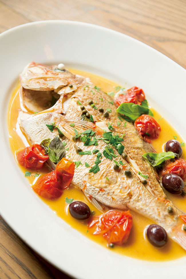 丸ごと1匹の魚をシチリア産のオリーブなどで煮込んだ「マダイのアックアディマーレ」¥3,500(時価)。ふっくらとした食感のマダイにソースが絡み、ペロリと平らげてしまう。脇を固めるのは、しっとりとした自家製天然酵母のパンや自然派のイタリアワイン。「バターを使った料理が多い北イタリアに滞在していたときは、新鮮な魚料理を求めて海のある土地まで出かけていました」と、オーナーの出雲択逸シェフ。