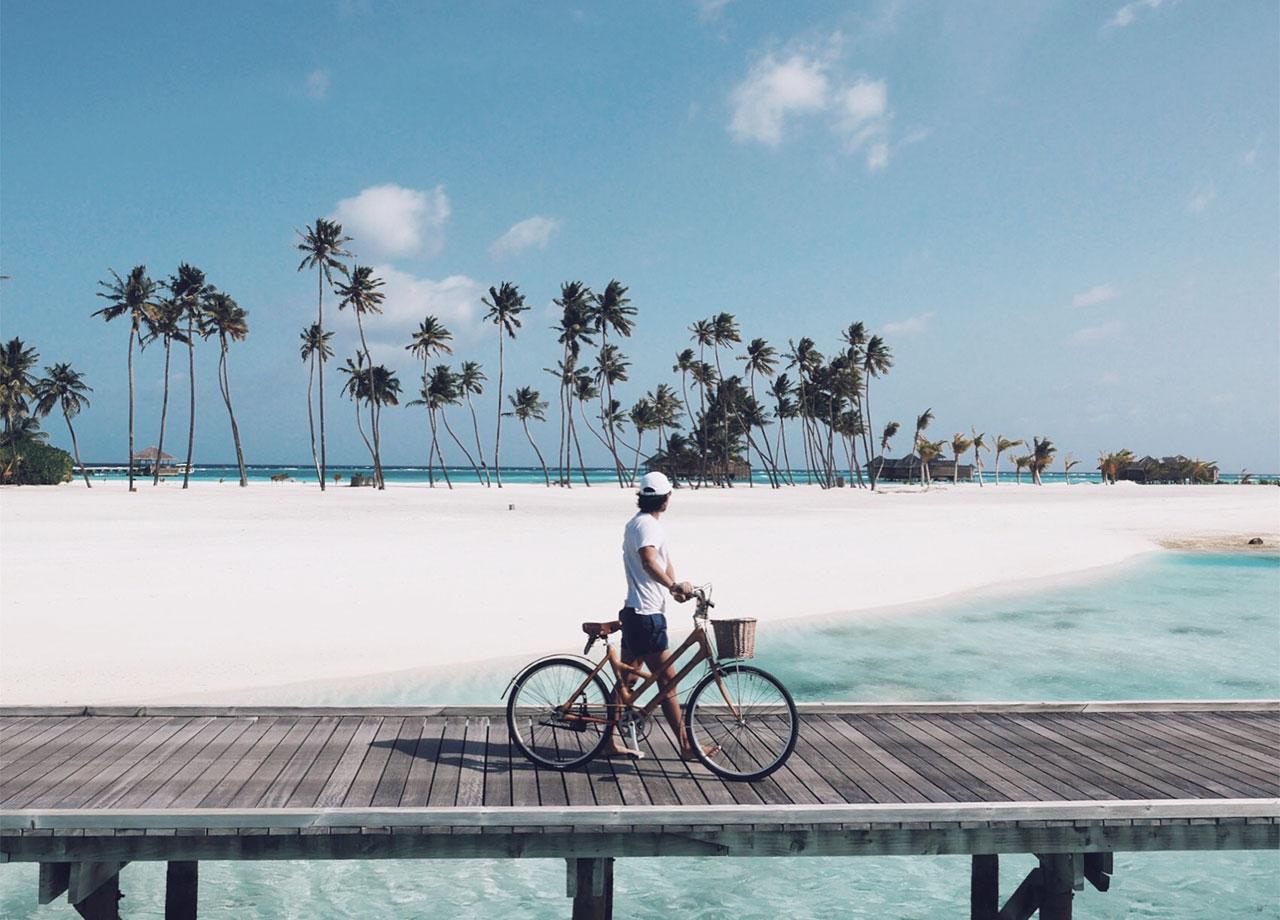 モルディブは一島丸ごとリゾートホテルになっていることが多い。水上コテージをつなぐ歩道で、海を背景にサイクリング。