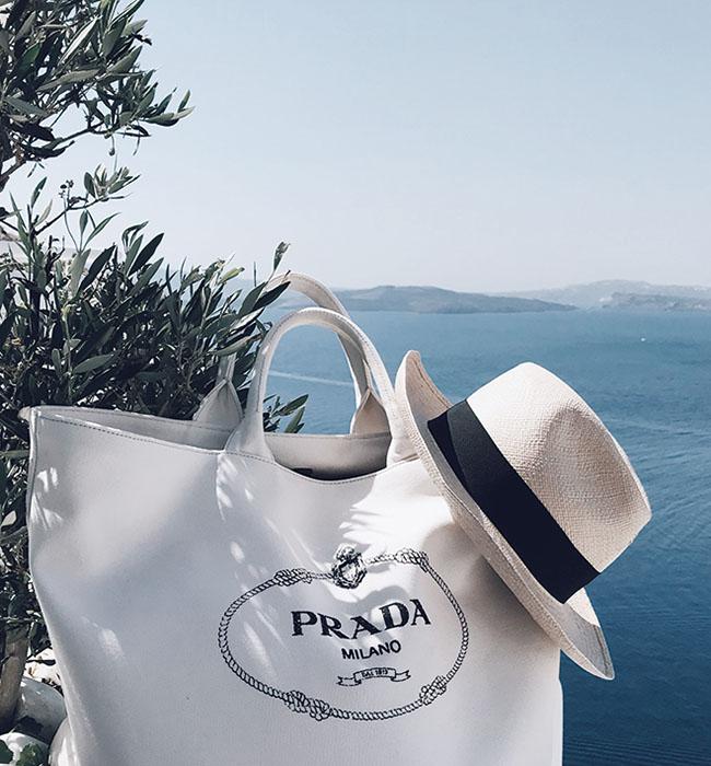 青い海と白い建物のコントラストが特徴のギリシャのサントリーニ島で。手持ちのアイテムもオケージョンに合わせてセレクト。