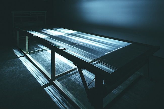 取材で撮影された2万枚におよぶ写真を、 高谷史郎のディレクションのもと映像作品で制作。 織機の糸に投影している。