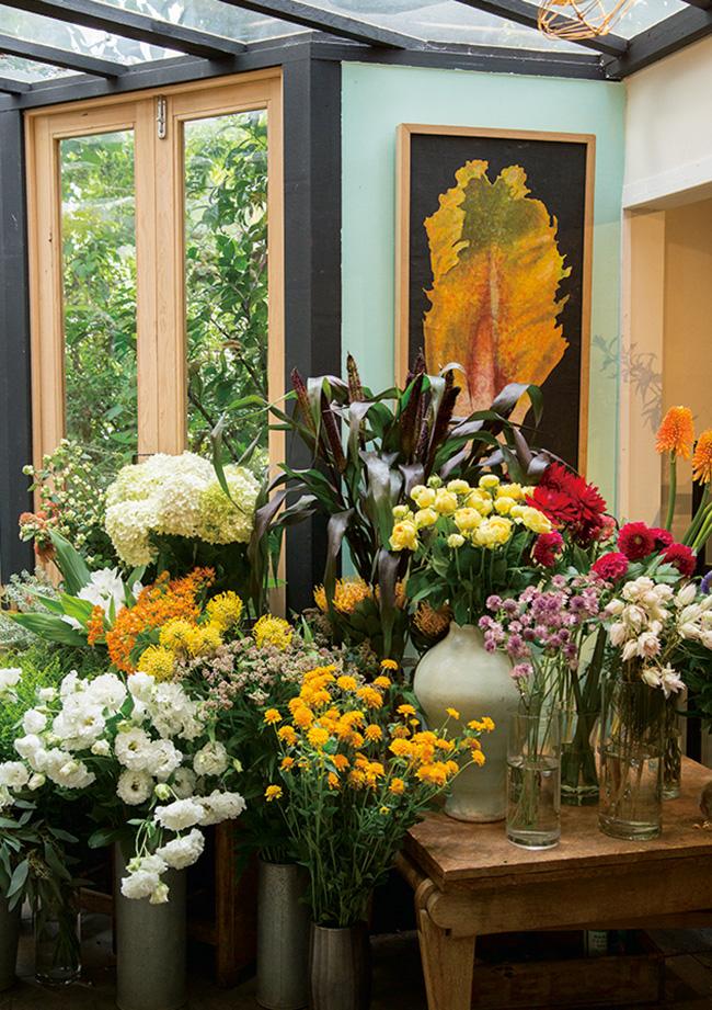 色とりどりの花とともに絵やオブジェが飾られている。
