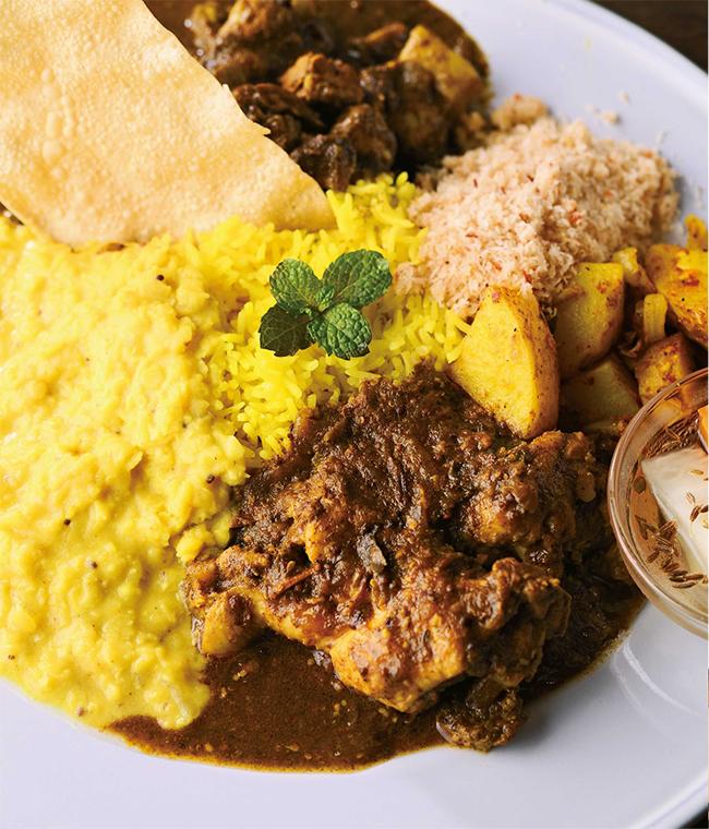 チキンカレー、ポークカレー、パリップ(レンズ豆)カレー、ライス、ポルサンボル(ライム風味のココナッツとチリパウダーの和え物)、パパダム、じゃがいものアラパドゥマ(スパイス炒め)、自家製ピクルスを盛り合わせた贅沢全部のせランチ(¥1,500)。セイロンティーまたはハーブティー(ヨモギ、ドクダミ、カキオドシから選べる)などが付くドリンクセットは¥1,700。