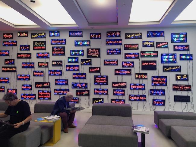 ロビーの壁一面に、世界各国の言葉で綴られた「ようこそ」のサインが点滅。PASCALE MARTHINE『WELCOME WALL』
