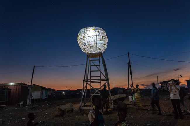 ゴミの荒野を照らす希望の光、ペットボトルで作った月を掲げた巨大オブジェ作品『ムーンタ<br /> ワー』。(2018-19年)撮影:長坂真護
