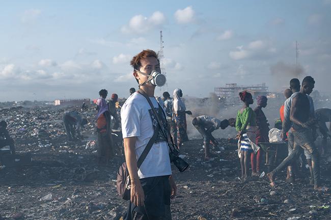 アグボグブロシー地区での活動風景より。有毒ガスで霞んだ電子ゴミの荒野にて。(2018-19年)撮影:福田秀世