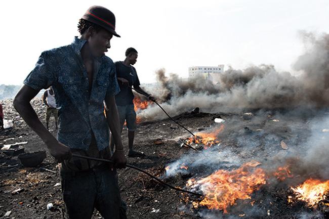 マスクもなく電子ゴミを燃やす人々。燃えかすから金属を取り出し、売ってわずかばかりの収入を得る。(2018-19年)撮影:福田秀世