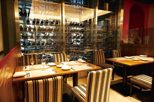 客席の隣にはワインが保管されたウォークインカーヴが。飲みたいワインを自ら選び、テーブルで楽しむスタイル。