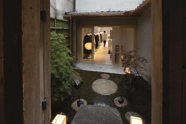 蔵の建物から見た苔の中庭と母屋。青竹の塀や銅製の雨樋など細部へのこだわりが。