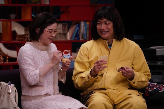 黄色いジャンプスーツに身を包んだ香取慎吾が演じる主人公、舎人真一。写真左は舎人の友人、曽我そと子役の宮澤エマ。©︎2020 Amazon Content Services LLC