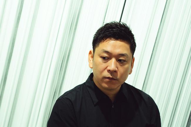 展示会場にて。背景の作品は『Moment』シリーズ(2020年)より。(Photo: Ayako Masunaga)