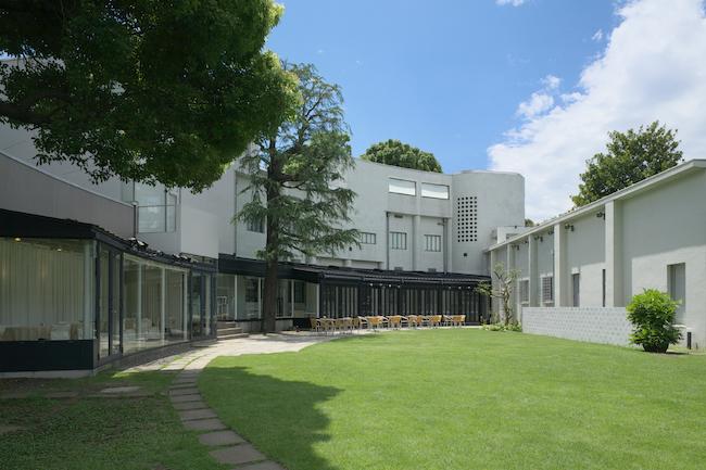 中庭より、弧を描くように建つ原美術館の建物。中央はカフェ ダールのオープンテラス席。(撮影:渡邉修)