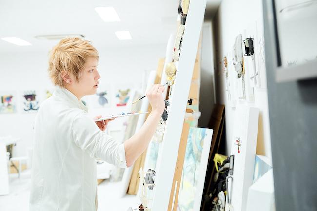 巨大なキャンバスを前に、真剣な面持ちで絵筆を握る手越祐也。