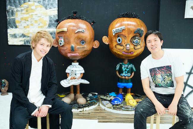 長坂真護のアトリエにて、ガーナの電子ゴミを使った長坂の立体作品の前で語り合う二人。