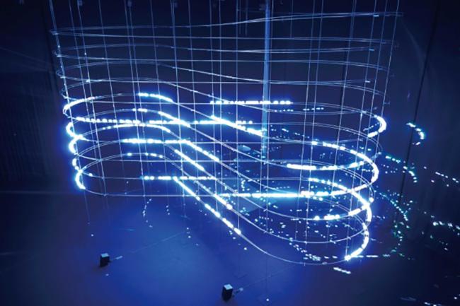 展覧会の展示風景より。螺旋状のレールを転がるボールを正確にトラッキングしてレーザーを照射、明滅する光と音響を体感させる大型インスタレーション。『particles 2021』2021「ライゾマティクス_マルティプレックス」展示風景 東京都現代美術館、2021年 Photo by Muryo Homma