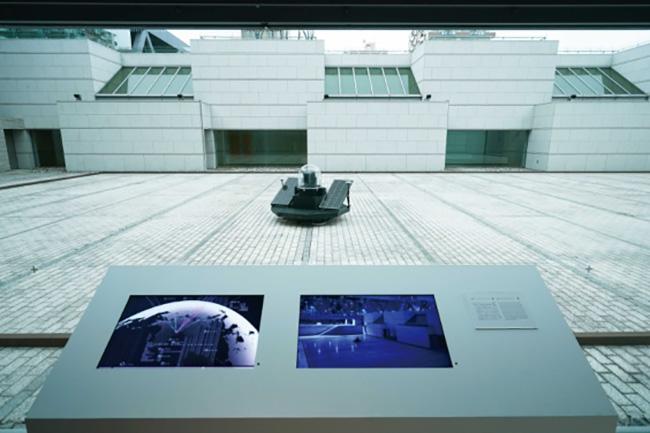 展覧会の展示風景より。人工衛星から取得した位置情報に基づき、美術館の中庭で自律的な活動を行うロボティクス。『RTK Laser Robotiks Experiment』2021 「ライゾマティクス_マルティプレックス」展示風景 東京都現代美術館、2021年 Photo by Muryo Homma