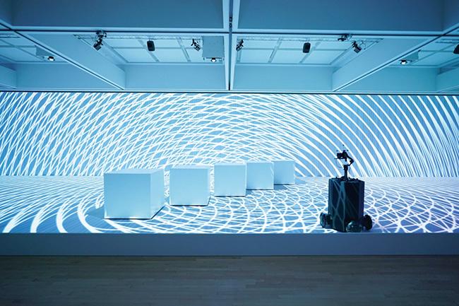 """展覧会の展示風景より。ダンサーの動きをモーションデータ化し、映像プロジェクションやキューブ型のロボティ<br /> クスとともに構成したインスタレーション。『Rhizomatiks × ELEVENPLAY""""multiplex""""』2021 「ライゾマティクス_マルティプレックス」展示風景 東京都現代美術館、2021年 Photo by Muryo Homma"""
