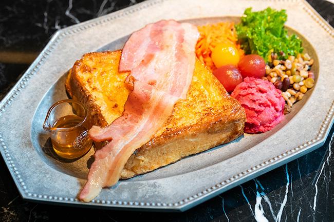 大きな鉄板で焼いてから表面をキャラメリゼするという、ひと手間かけたフレンチトースト。原木ベーコンとオレンジ蜂蜜の甘じょっぱさがやみつきに!「お食事フレンチトーストプレート」¥1,600