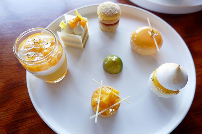 左から時計回りに:「マンゴーとココナッツのブランマンジェ」、「エキゾチッククリームチーズケーキ」、「ココナッツとパイナップルのパウンドケーキ」、「ココナッツムース、マンゴーと生姜のジュレ」、「パッションフルーツとレモン、メレンゲのケーキ」、「マンゴーと柚子のタルト」、「ベルガモット風味のショコラ」